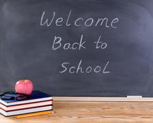 Student desktop and erased black chalkboard with welcome back to school messa - stock photo