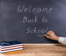 Teacher hand putting smile symbol on welcome message to students on erased bl - stock photo