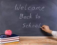 Teacher hand writing on erased black chalkboard. Desktop with books, apple, p - stock photo