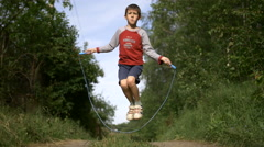 Boy jumping rope outdoors Stock Footage