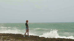 Attractive young woman with long red hair standing on the coast and looking to Stock Footage