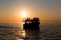 Ferry boat silhouette with passengers - stock photo