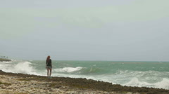 Attractive young woman with long red hair standing on the beach near the storm Stock Footage