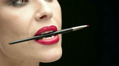 Red Lipped Woman Holding Makeup Brush in Her Mouth - stock footage