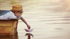 Boy places a paper boat on the water's surface and blows for it to sail away Stock Footage