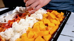 A cook peppers the vegetables laid out on the oven-tray before cooking Stock Footage