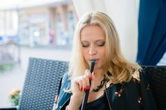 Beautiful young woman smoking hookah shisha nargile and drinking tea in a street Stock Photos