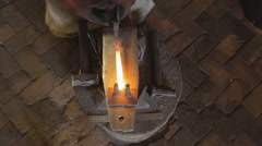 Blacksmith bends a red hot metal billet using a fork Stock Footage