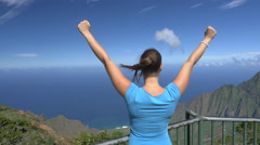 CLOSE UP: Happy young woman on lookout point outstretching arms victoriously - stock footage