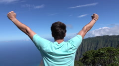 SLOW MOTION: Cheerful young man on mountaintop outstretching arms proudly Stock Footage