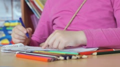 The little girl draws the pictures in the copybook Stock Footage
