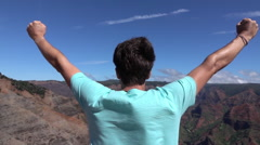 SLOW MOTION: Happy man on top of the mountain outstretching arms victoriously - stock footage