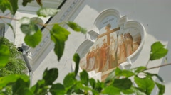 Religious Image on a Gable of Small Church Sunny Day Courtyard Fresh Green Stock Footage