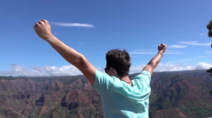 SLOW MOTION: Man standing on the edge of canyon, victoriously raising arms Stock Footage