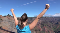 SLOW MOTION: Cheerful young woman on mountain peak outstretching arms cheerfully - stock footage