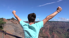 SLOW MOTION: Happy young man on top of the mountain raising arms proudly Stock Footage