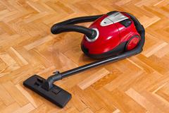 Vacuum cleaner on parquet - stock photo