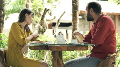 Offended couple sitting by table in cafe outdoor with exotic garden Stock Footage