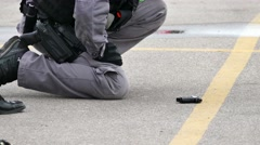 Tactical police office bending over gun on the ground Stock Footage