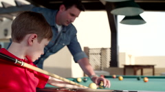 Father teaching his son billiard. - stock footage