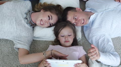 Happy family using digital tablet on floor at home - stock footage