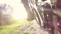 Cyclist man rides through the forest sunlight, low wide angle - stock footage