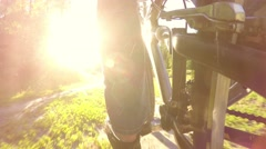 Cyclist rides through the forest sunlight, low wide angle - stock footage