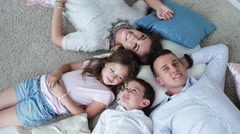 Family portrait with heads together lying on the floor Stock Footage