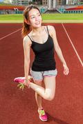 Chinese female athelete stretching legs on sports field, warming up Stock Photos