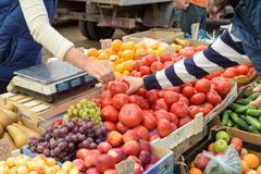 Local vegetable market stall selling fresh produce with peoples arms choosing - stock photo
