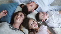 Smiling family of four lying on the floor, view from the top - stock footage