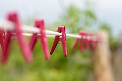 Red plastic domestic washing pegs on a white rope washing line outdoors - stock photo