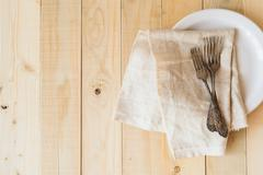 Top view three antique forks and napkin on white plate - stock photo