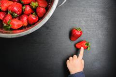 black desk background with copyspace, the child picks strawberries - stock photo