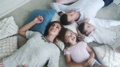 Smiling family of four lying on the floor, view from the top Stock Footage