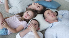 laughing family of four lying on the floor, view from the top - stock footage