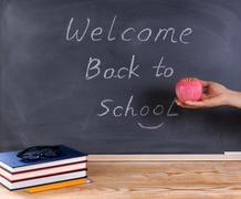 Teacher hand holding red apple with erased black chalkboard and desktop in im Kuvituskuvat