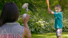 Little boy hitting a home run in his backyard Stock Footage