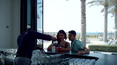 Bartender serving drinks to Expat couple at counter. Stock Footage
