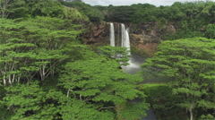 AERIAL: Majestic waterfall in the middle of lush jungle in Hawaii - stock footage