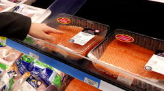 Woman selecting atlantic salmon fillet inside Walmart store Stock Footage