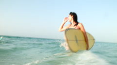 Expat woman carrying surfboard at sea. Stock Footage