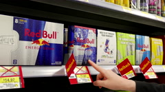 Woman buying Red Bull energy drink inside Walmart store - stock footage