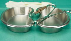 Surgical clamp and knife placed on stainless kidney shape bowl - stock photo