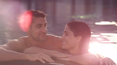 Expat couple at the edge of swimming pool. - stock footage