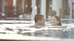 Expat couple at swimming pool. Stock Footage