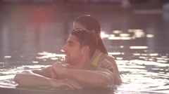 Expat couple at the edge of swimming pool. Stock Footage