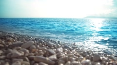 Sea, peeble shore and waves. Seascape at sunset in slow motion. Stock Footage