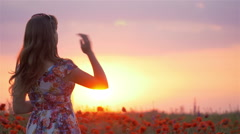 Young beautiful woman with raised arms in spring field - stock footage