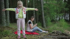 Small girl in the forest with mother. Happy child is hugging imaginary person. Stock Footage